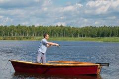 En man i gula exponeringsglas, i ett fartyg med åror, i mitten av sjön, rymmer en fiska pol för att fånga en stor fisk, under a royaltyfria foton