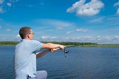 En man i gula exponeringsglas, kastar en metspö i sjön, för att fiska, på bakgrunden av ett härligt landskap royaltyfri fotografi