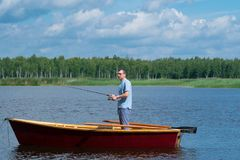 En man i gula exponeringsglas, på ett fartyg med åror som rymmer en metspö och fiskar i mitt av sjön, mot ett härligt arkivfoton