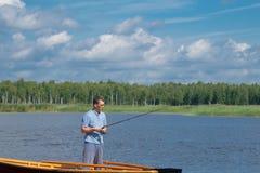 En man i gula exponeringsglas, på ett fartyg som rymmer en metspö och fiskar i mitt av sjön, mot ett härligt landskap royaltyfri bild