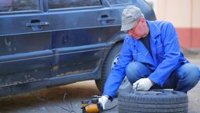 En man i handskar pumpar en kompressor för bilgummihjul till en skiva arkivfilmer