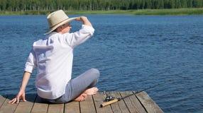 En man i en hatt och att sitta på pir och att se in i avståndet som ligger bredvid en metspö, mot sjön arkivbild