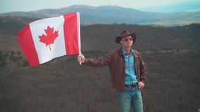 En man i en hatt och solglasögon, piskar omslaget och jeans som rymmer en kanadensisk flagga arkivfilmer