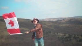 En man i en hatt och solglasögon, piskar omslaget och jeans som rymmer en kanadensisk flagga lager videofilmer