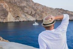 En man i en hatt och en vitskjorta sitter med hans baksida på kusten och stirrar på yachten royaltyfri foto