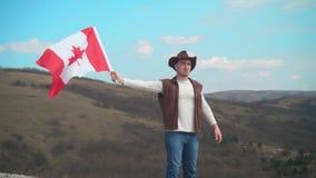 En man i en hatt, en v?st och ett l?deromslag och jeans rymmer en kanadensisk flagga Flaggan av Kanada framkallar i vinden arkivfilmer