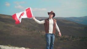 En man i en hatt, en v?st och ett l?deromslag och jeans rymmer en kanadensisk flagga Flaggan av Kanada framkallar i vinden stock video