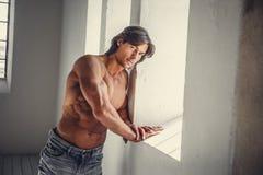 En man i jeans som poserar nära fönster i naturligt dagsljus Royaltyfri Bild