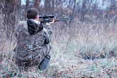 En man i kamouflage och med ett jaktgevär i en skog på en sp royaltyfri foto