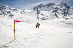 En man i kamouflagevinterlag som går på snön med bakgrunden av snöberget Royaltyfri Bild