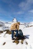 En man i kamouflagevinterlag ställer in - upp hans ryggsäck som framme står av bakgrunden av Matterhorn, Royaltyfria Bilder