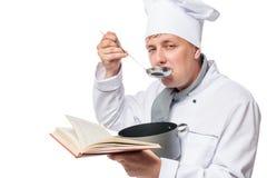 En man i kockar för en dräkt med en kruka av soppa arkivfoton