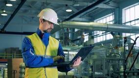 En man i likformig som skriver på en bärbar dator, fabriksarbetare stock video