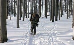 En man i likformign som går till och med vinterskog Arkivfoton