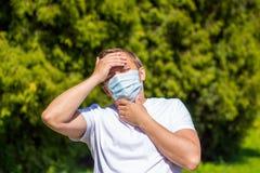 En man i en maskering fr?n allergi, i en vit T-tr?ja, st?llningar i parkerar royaltyfri fotografi