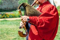 En man i en medeltida röd dräkt spelar på säckpipe- royaltyfria foton