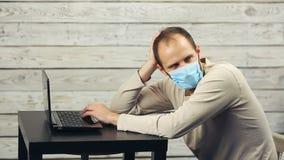 En man i medicinska arbeten f?r en maskering p? datoren och hostorna stock video