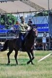 En man i militär likformig rider en häst Royaltyfri Bild