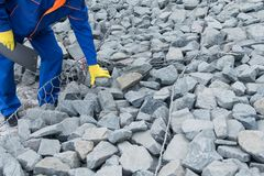 En man i overaller kontrollerar en sten på en vägkonstruktion royaltyfri bild