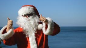 En man i en Santa Claus dräkt dansar på kusten Lopp och semester stock video
