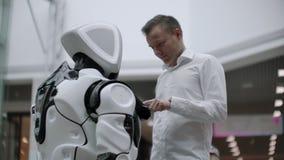 En man i en skjorta meddelar med en vit robot som frågar frågor och trycker på skärmen med hans fingrar lager videofilmer