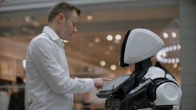 En man i en skjorta meddelar med en vit robot som frågar frågor och trycker på skärmen med hans fingrar stock video