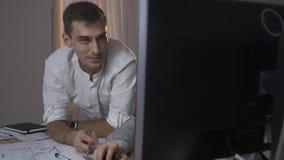 En man i en skjorta sitter på datoren, och punkter med en blyertspenna i bildskärmen, de två männen arbetar i övertid stock video