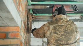 En man i skyddande hörlurar borrar en tegelstenvägg för att lägga ventilationsrör lager videofilmer