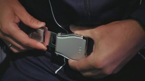 En man i en sportdräkt är fäst med en säkerhetsbälte i ett flygplan HD 1920x1080 långsam rörelse stock video