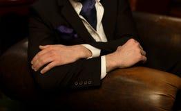 En man i en svart dräkt sitter i en stol händer vek på baksidan av stolen händer av en man i en dräkt på en stol stil royaltyfri fotografi