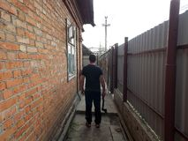 En man i svart med en yxa promenerar en tegelstenvägg och staket fotografering för bildbyråer