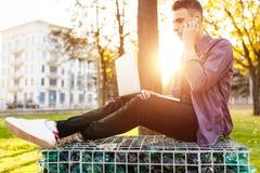 En man i tillfällig kläder sitter på en bänk, arbetar med en bärbar dator och royaltyfri bild