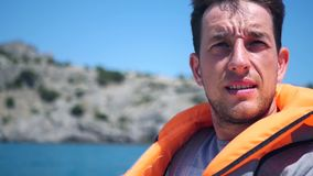 En man i en väst på ett fartyg skelar mot den ljusa solen HD 1920x1080 långsam rörelse lager videofilmer