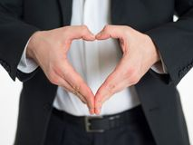 En man i en visning för affärsdräkt tummar upp teckenhjärta Royaltyfri Fotografi