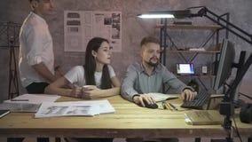 En man i en vit skjorta kommer med hans kollegor dokument, ett par av anställda sitter på en dator, teamwork arkivfilmer