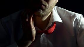 En man i en vit skjorta med ett band och ett skägg trycker på och skrapar hans skägg, närbilden, svart bakgrund, affärsman stock video