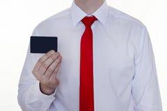 En man i en vit skjorta och ett rött band rymmer en ren kreditkort för inskriften, vit bakgrund royaltyfria bilder