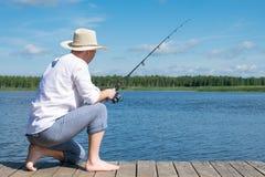 En man i en vit skjorta och hatt fiskar på sjön på en solig dag, bakre sikt arkivfoto
