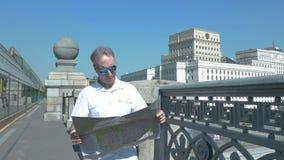 En man i en vit skjorta står på en bro och ser en pappers- översikt av staden stock video