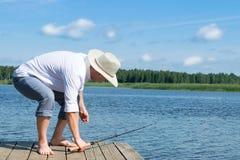 En man i en vit skjorta tar rotering för att fiska på sjön royaltyfri fotografi