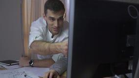 En man i en vit skjorta visar en blyertspenna i bildskärmen, bet ultrarapid stock video