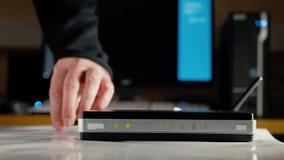 En man justerar antennerna på den WiFi routeren och överför dem till rätten