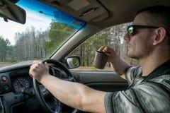 En man kör en bil och rymmer en kopp kaffe i hans hand arkivbilder