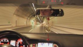 En man kör en bil på natten och drev till och med en tunnel arkivfilmer