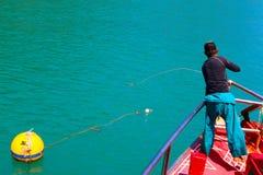 En man kastar ett rep för att binda upp turnerafartyget med boj Royaltyfria Foton