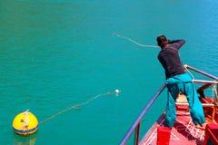 En man kastar ett rep för att binda upp turnerafartyget med boj Arkivfoto