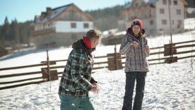 En man kastar snö på hans flickvän under varm vinterdag Barnet som paret spelar, kastar snöboll kamp arkivfilmer