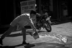 En man kastar vatten på de dammiga gatorna av Katmandu, Nepal Arkivbild