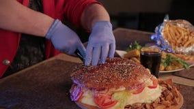 En man klipper en enorm hamburgare med en kniv stock video