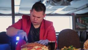 En man klipper en enorm hamburgare med en kniv arkivfilmer